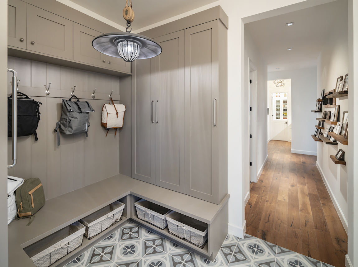 Grey colored mudroom with hooks for hanging clothes.