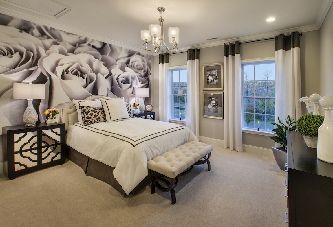 A guest bedroom with white bed covers and white curtains.
