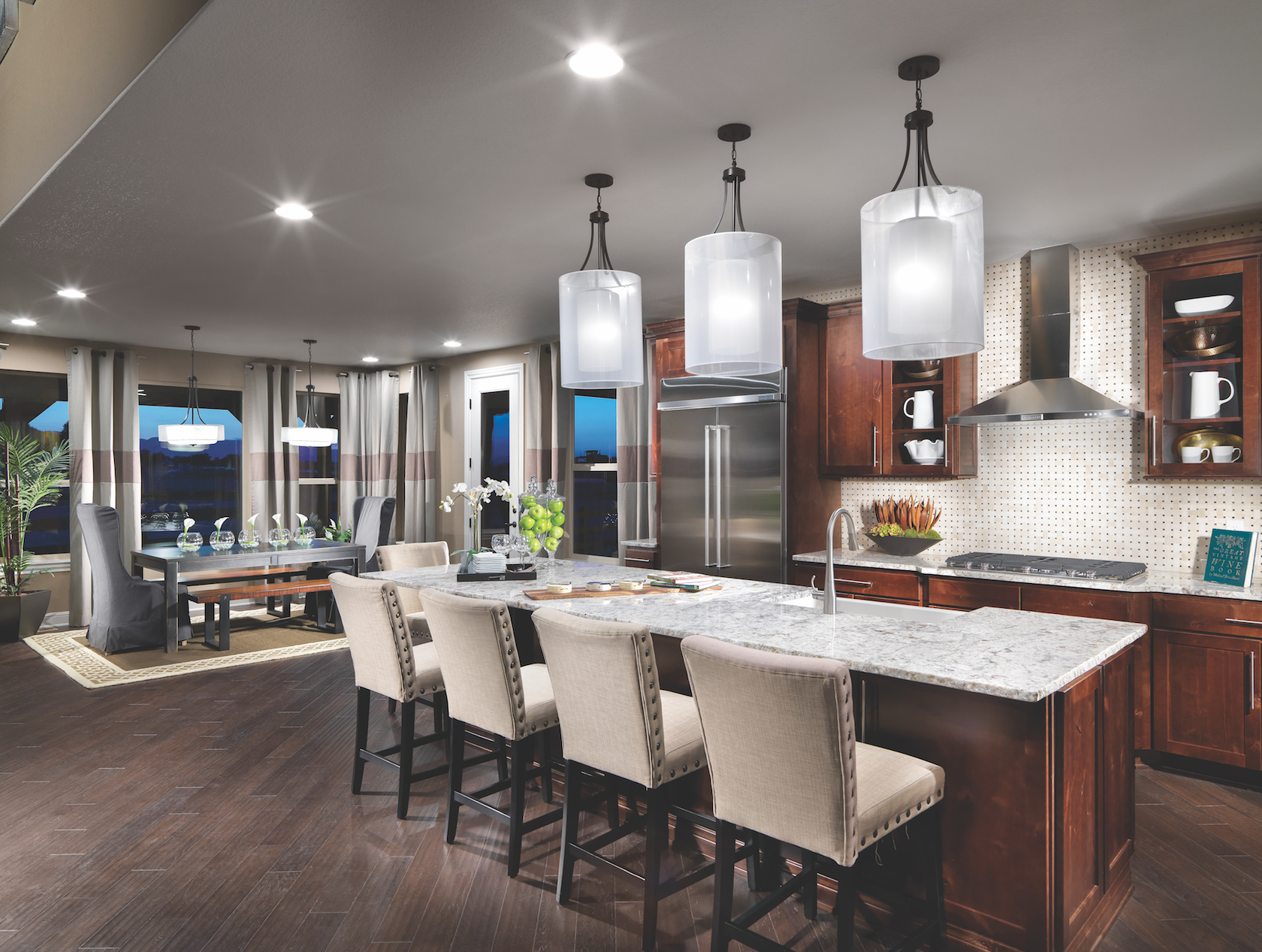 A modern kitchen with light fixtures hanging over the center island.