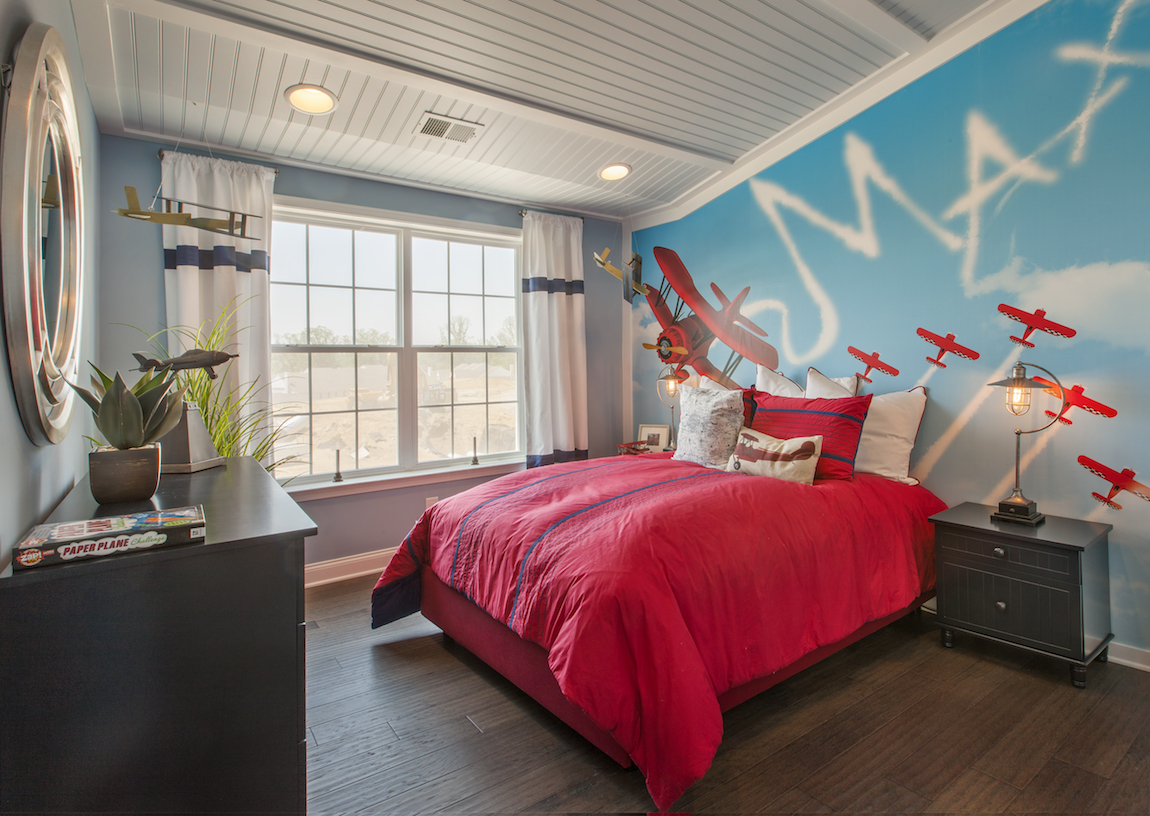 A child's bedroom with a red bed cover.