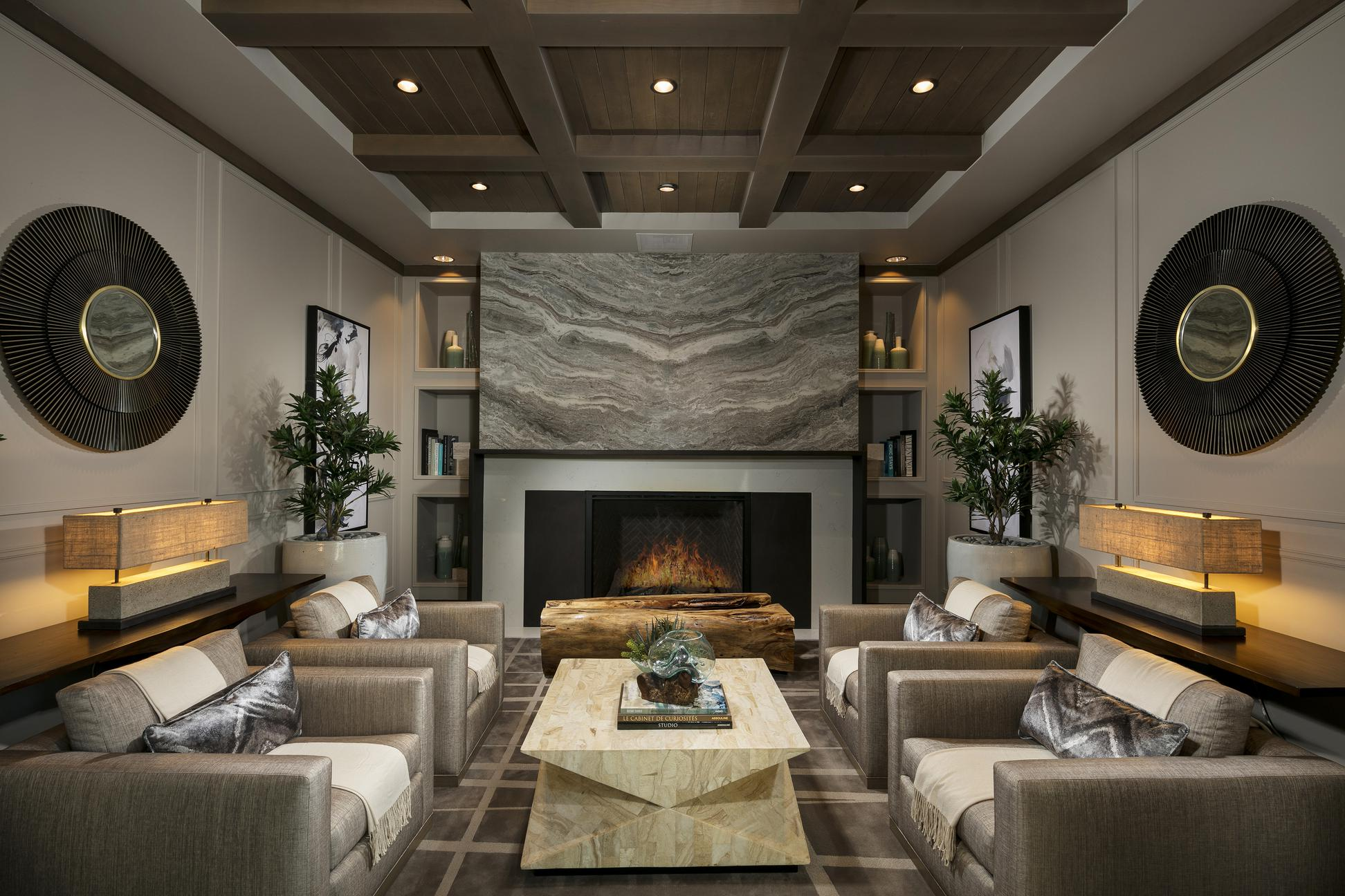 Living room with four large chairs in front of a fireplace.