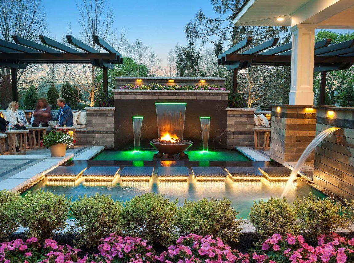 backyard pool with fountains and lighting
