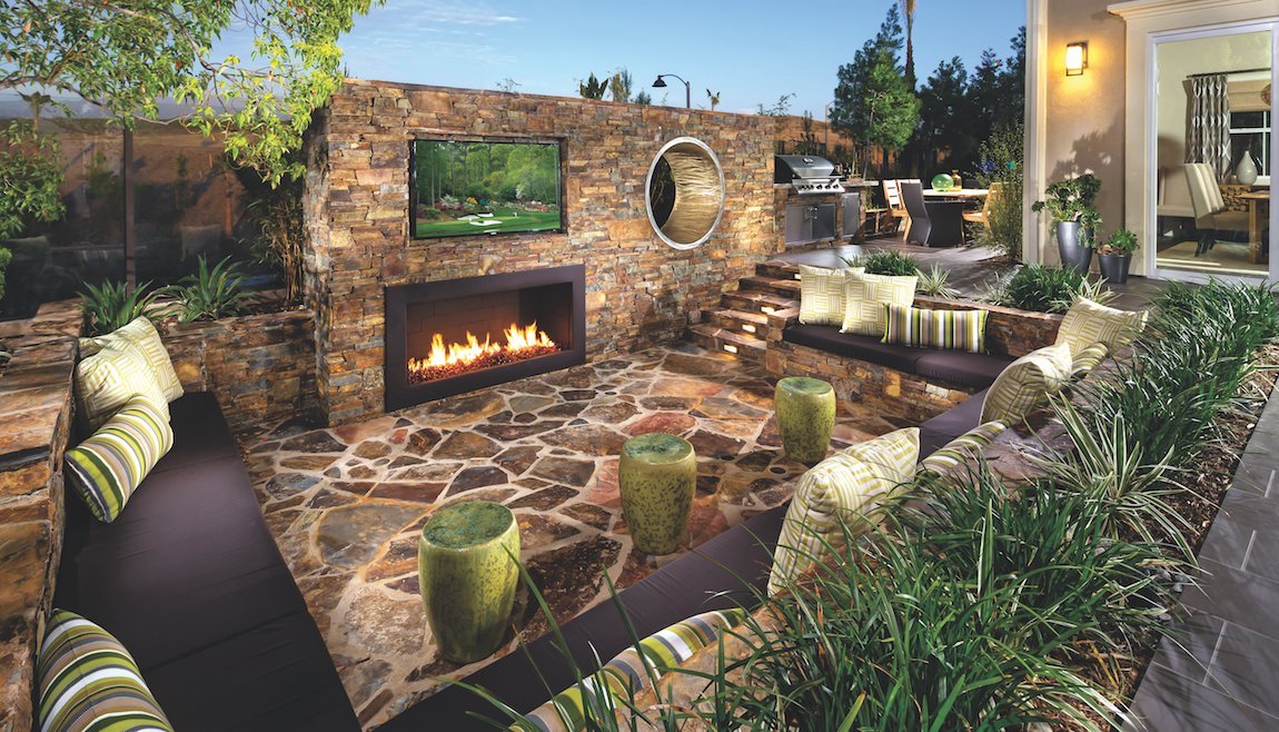 Backyard with couches, fireplace, television and serene outdoor lighting.