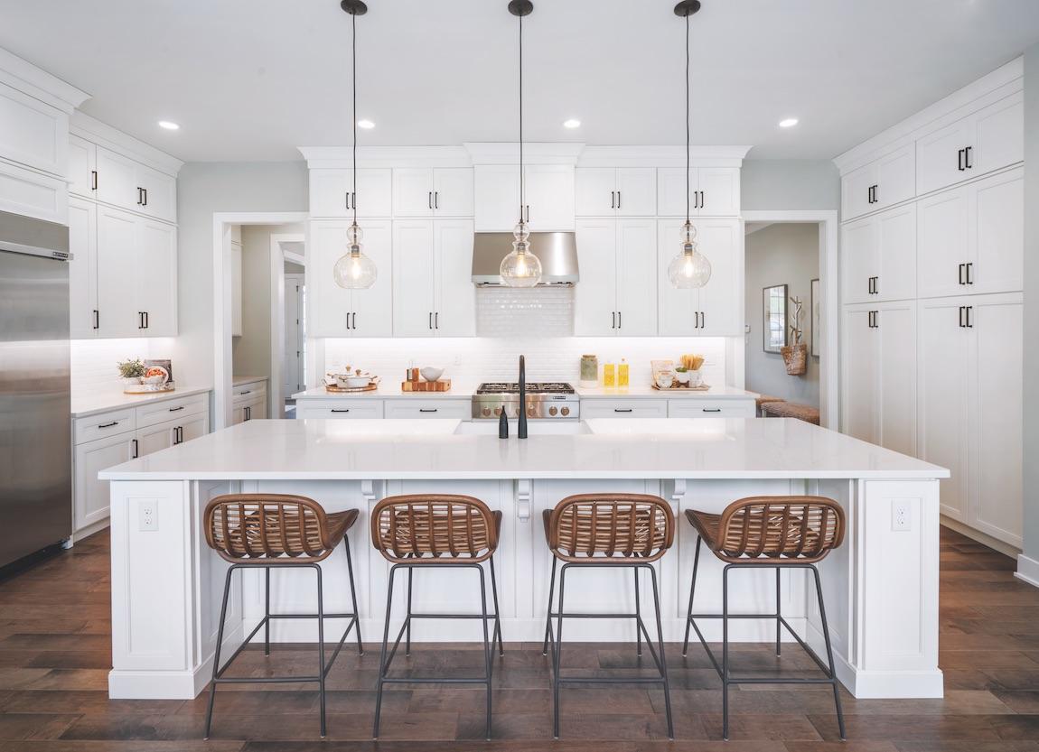 White kitchen with wicker island chairs.