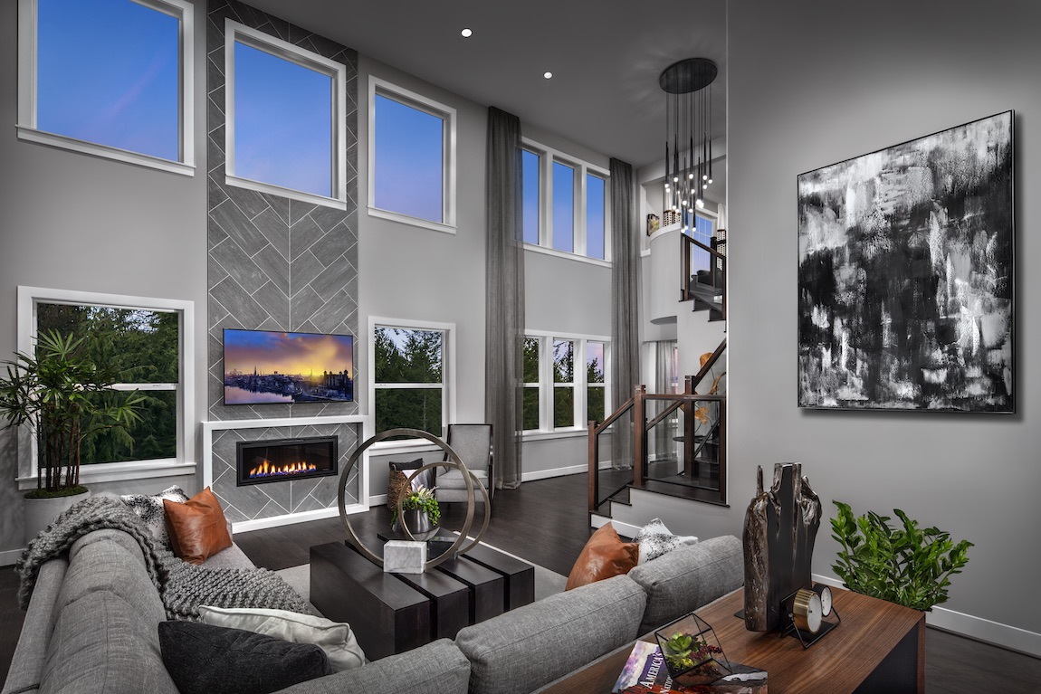 Great room with fireplace, many windows and gray color scheme.