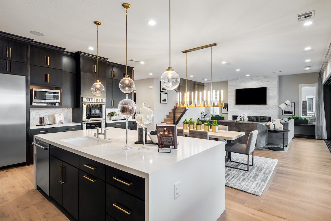 Kitchen with waterfall countertop island and black and white color scheme.