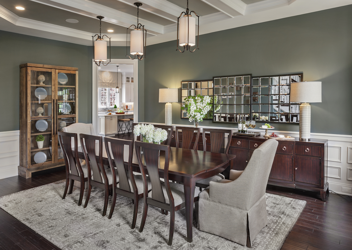 A luxury dining room with green colored walls and a chandelier.