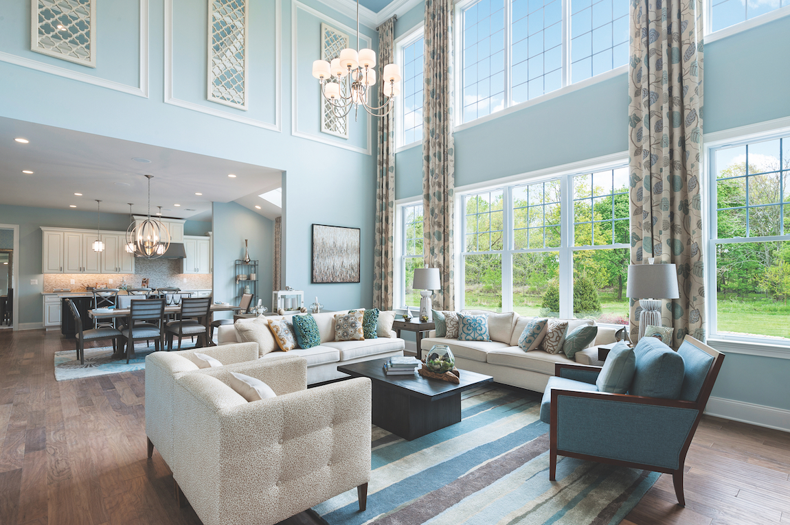 A luxury home with teal colored walls, a chandelier and tall ceilings.