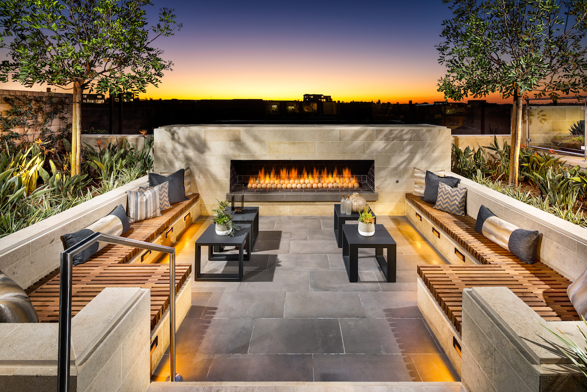 Outdoor sunken fire pit with lighting around the outdoor couches.