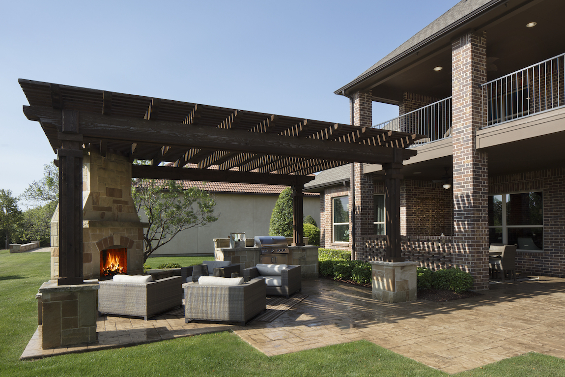 A suburban home in Texas with an outdoor fireplace on the patio.