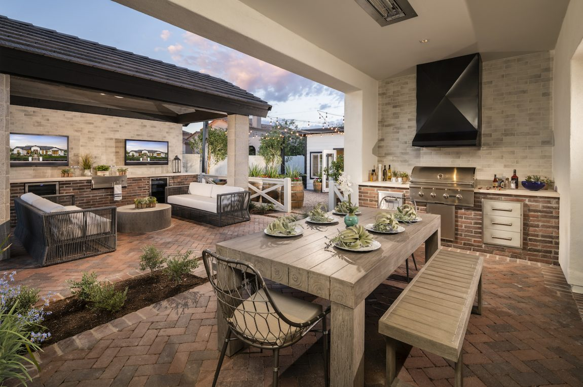 Outdoor patio wit grill and couches.