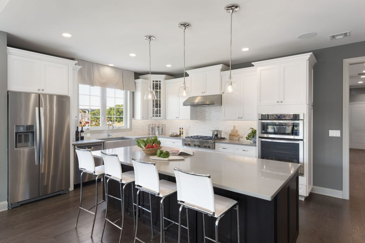 Modern kitchen with grey walls and white cabinets.