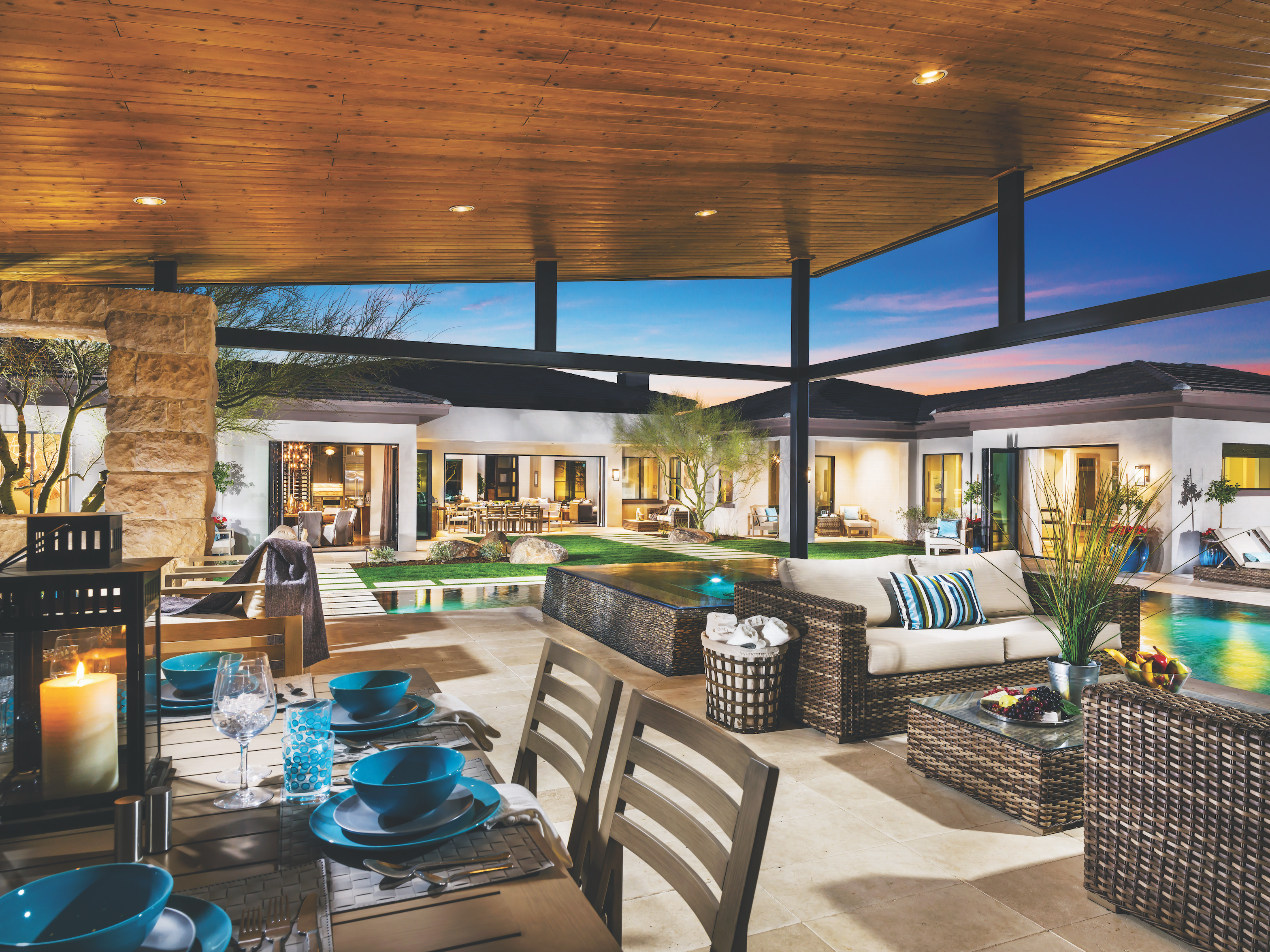 Covered outdoor seating in a backyard and outdoor lighting.