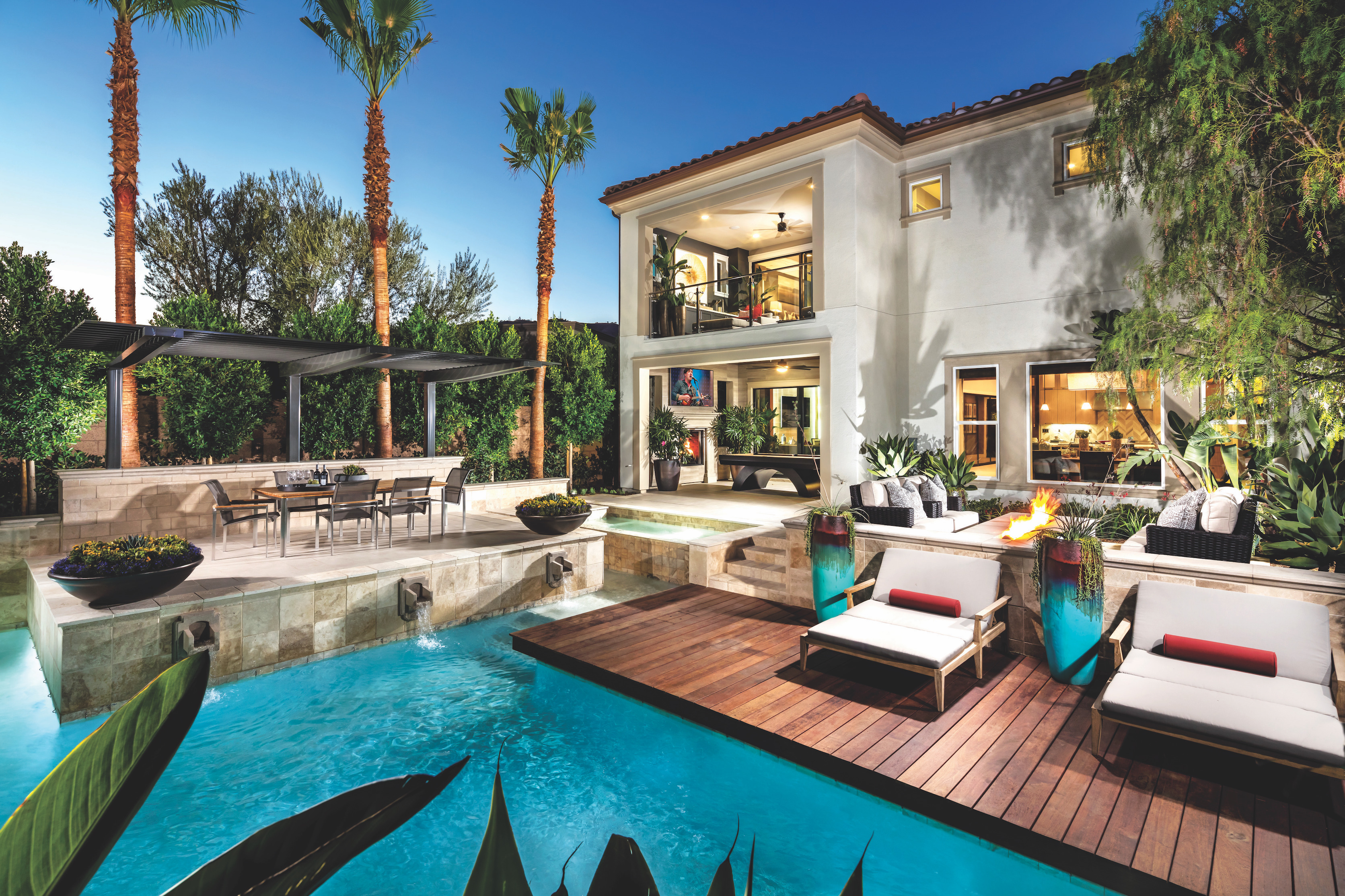 A luxurious backyard with a pool and outdoor lighting.