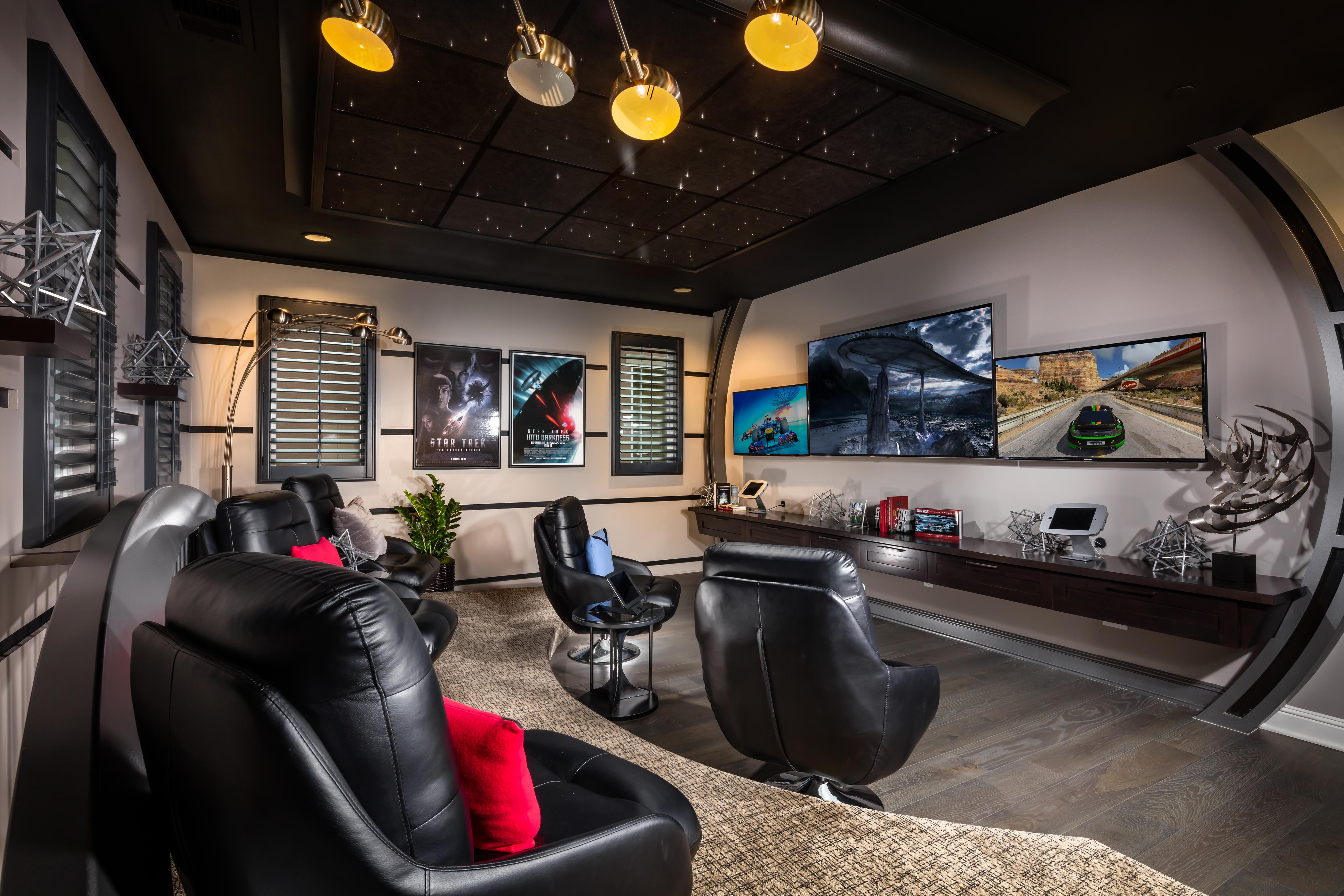 A home theater with three tv's and gaming station.