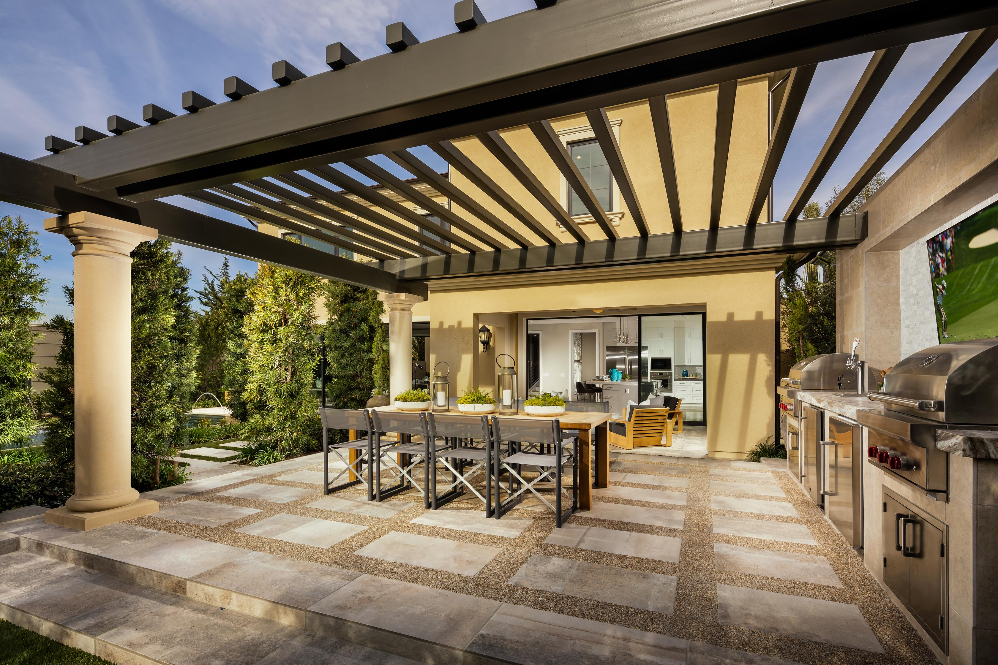 Outdoor living area with grill and a table with seating.