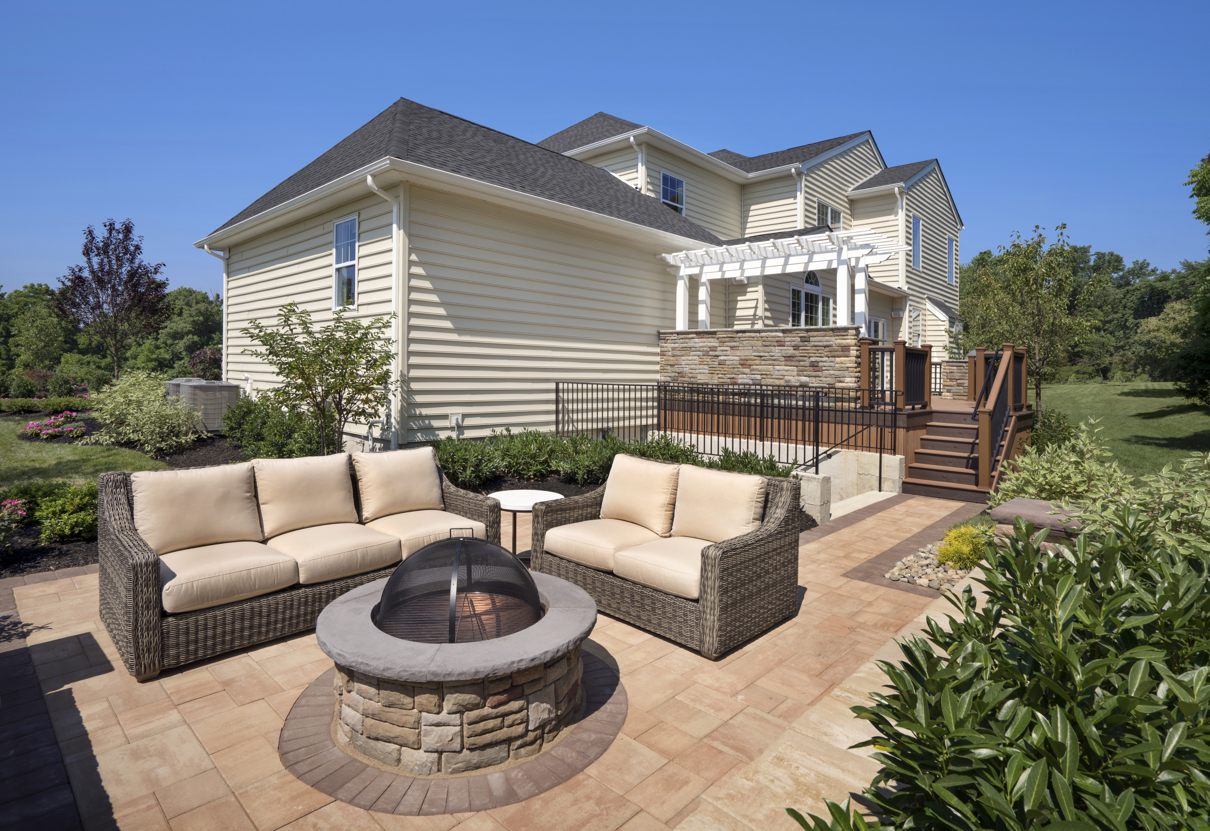 Outdoor living space with seating and a fire pit in a suburban home's backyard.