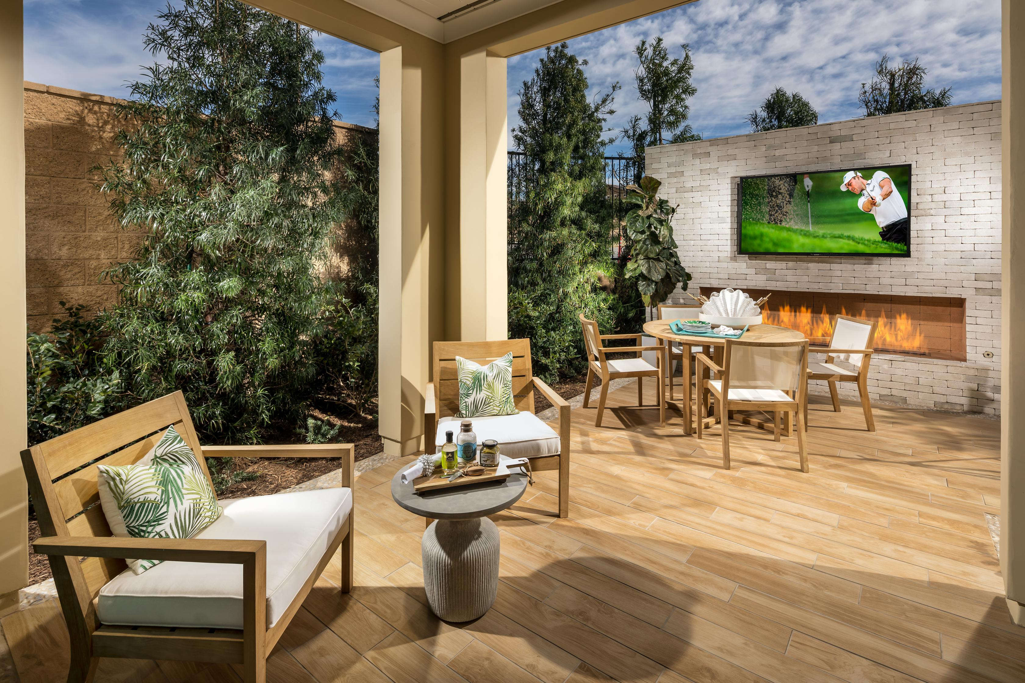 Covered outdoor living space with seating, fire pit and a tv.