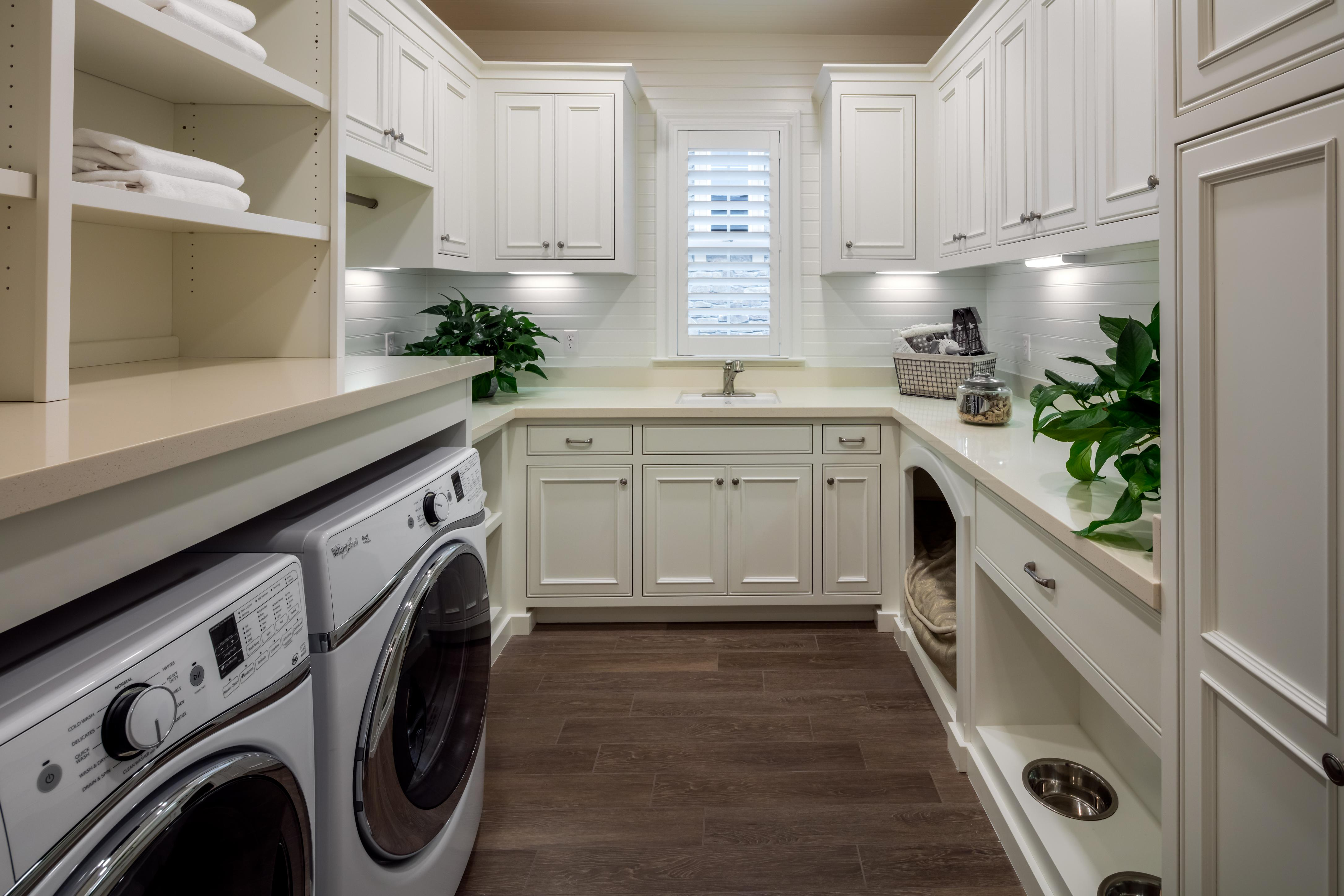 Laundry room with white cabinets and wood floors.