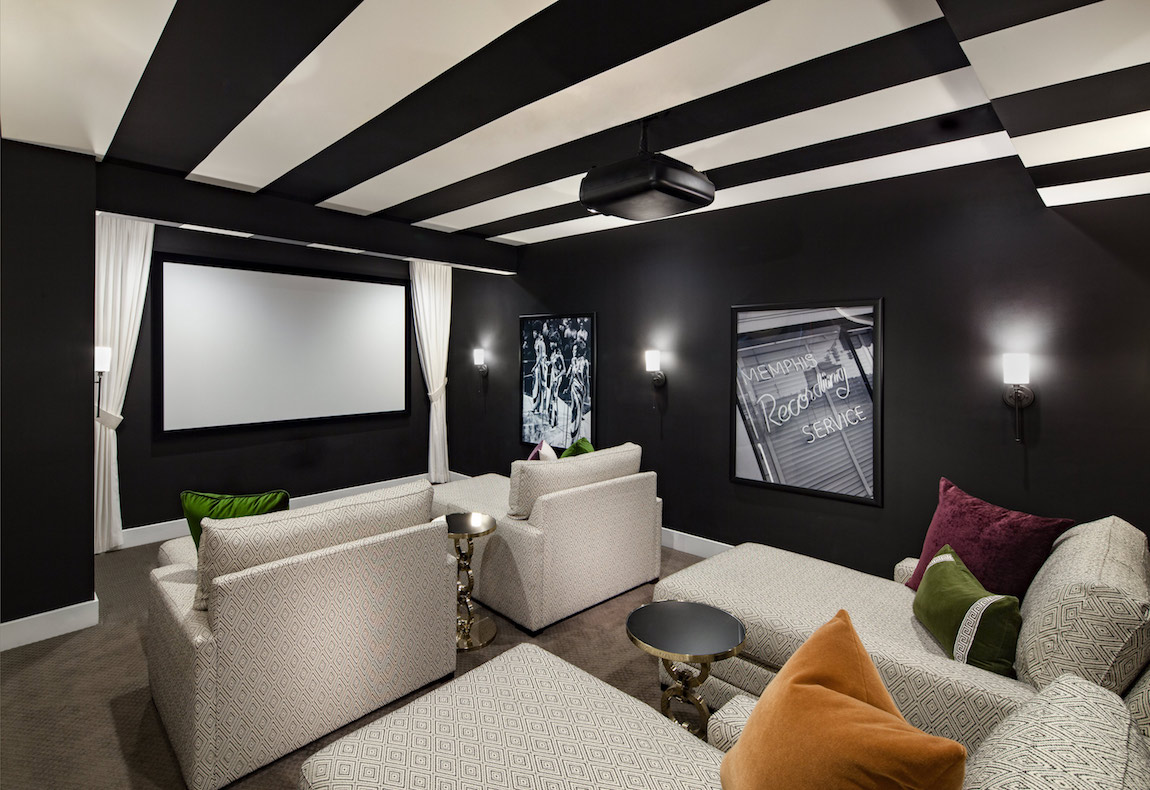 A home theater with four large theater chairs and a large screen.