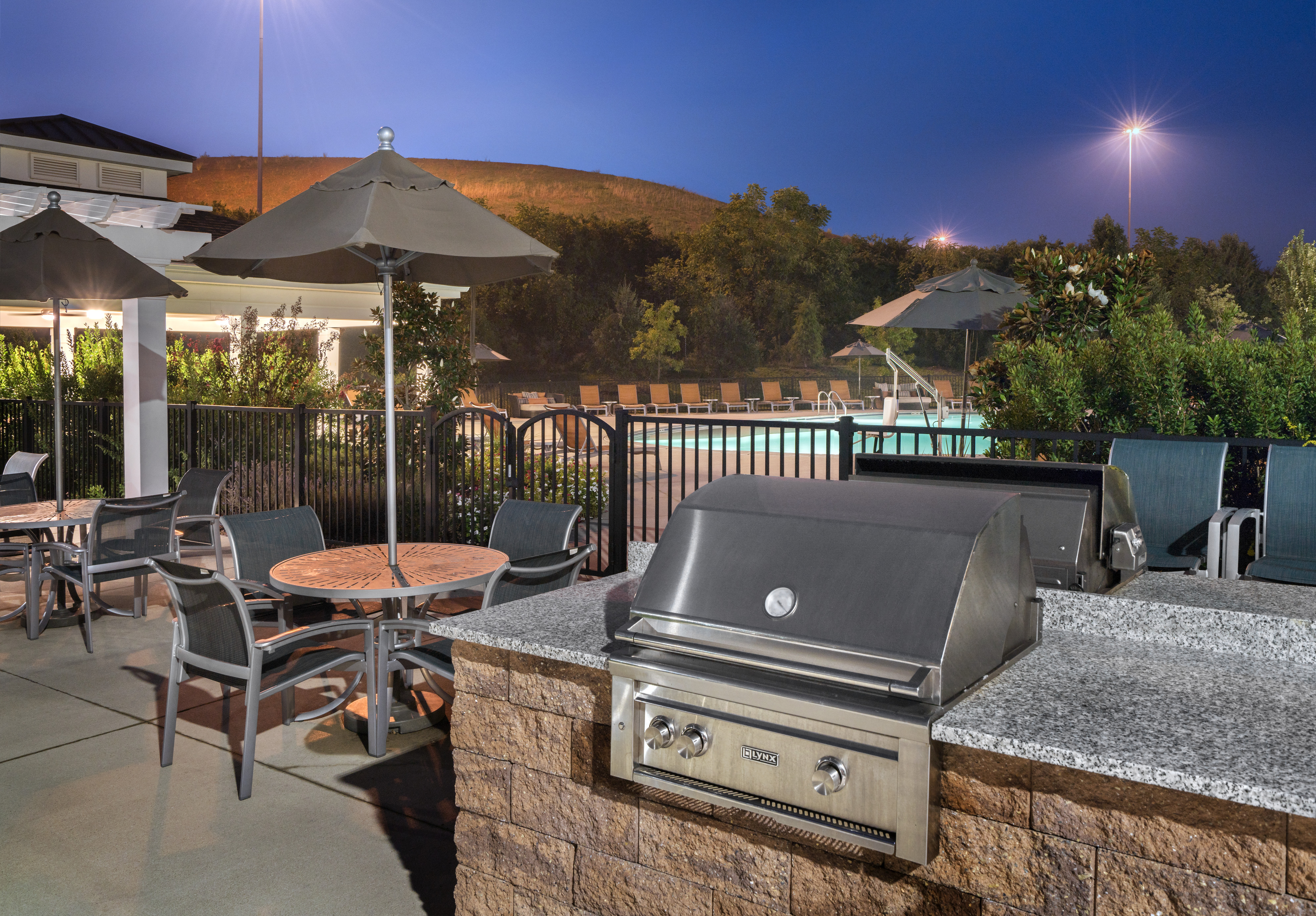 Grilling area and a pool in an apartment complex.