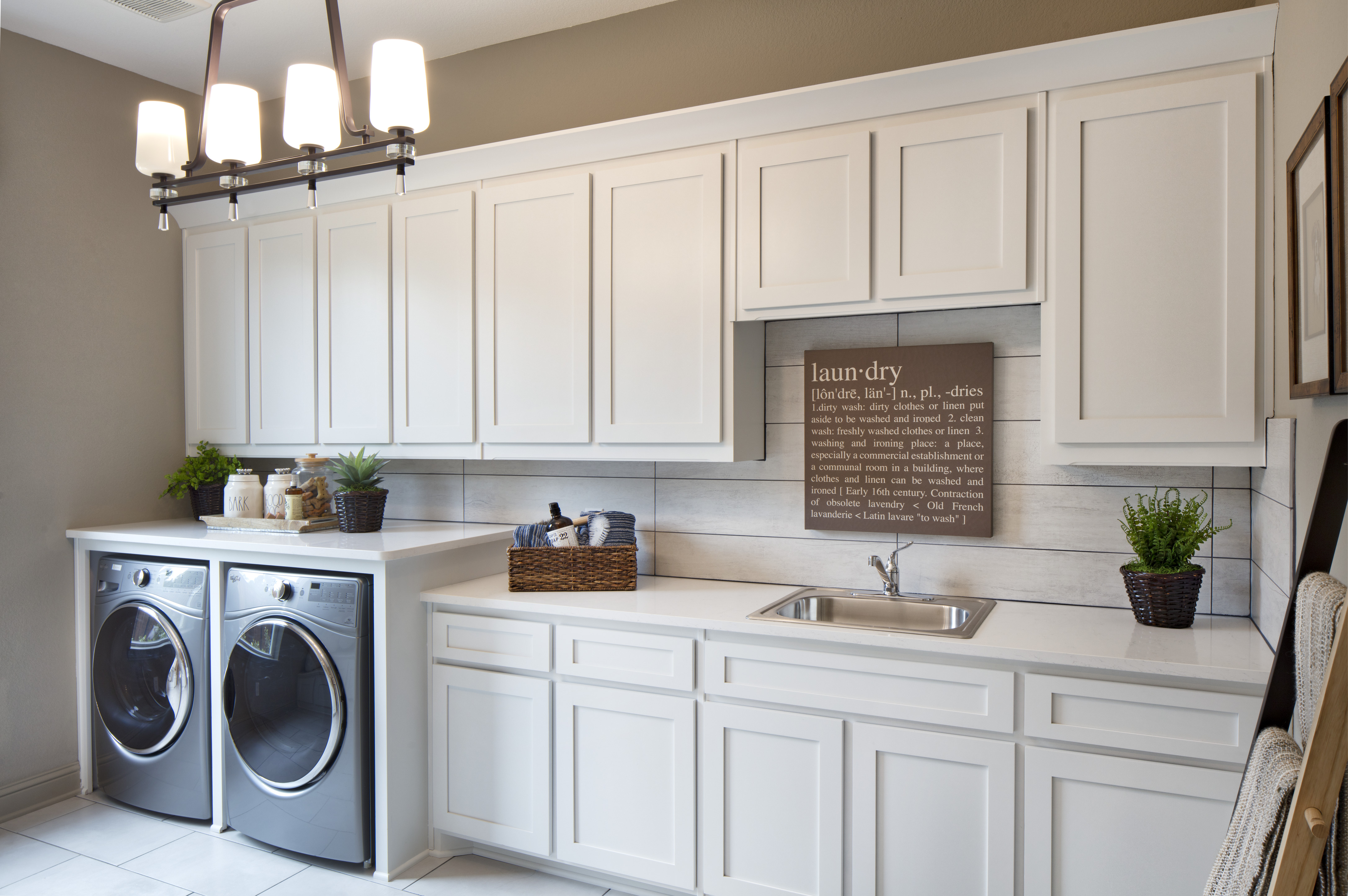 Mudroom with washer and dryer and white cabinets