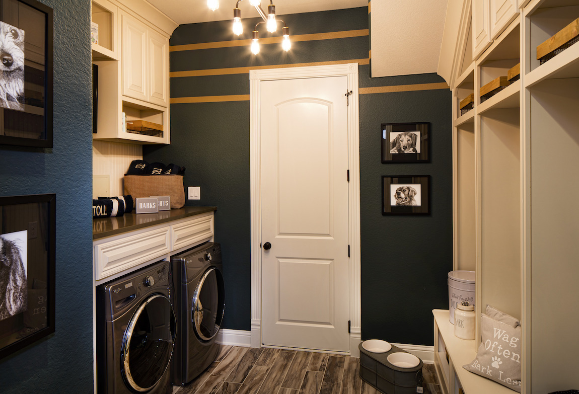 Laundry room with green and yellow paint color on walls in stripped pattern.