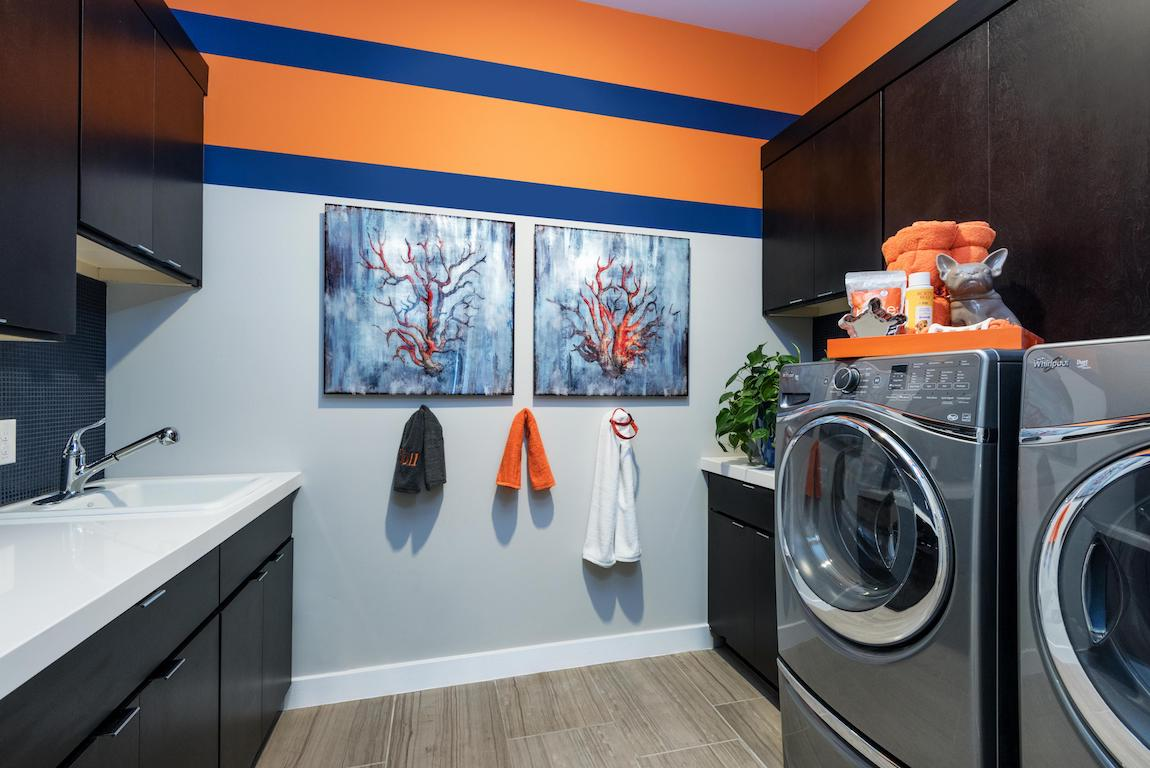 Laundry room with orange and blue colors painted on the wall in a stripped pattern.