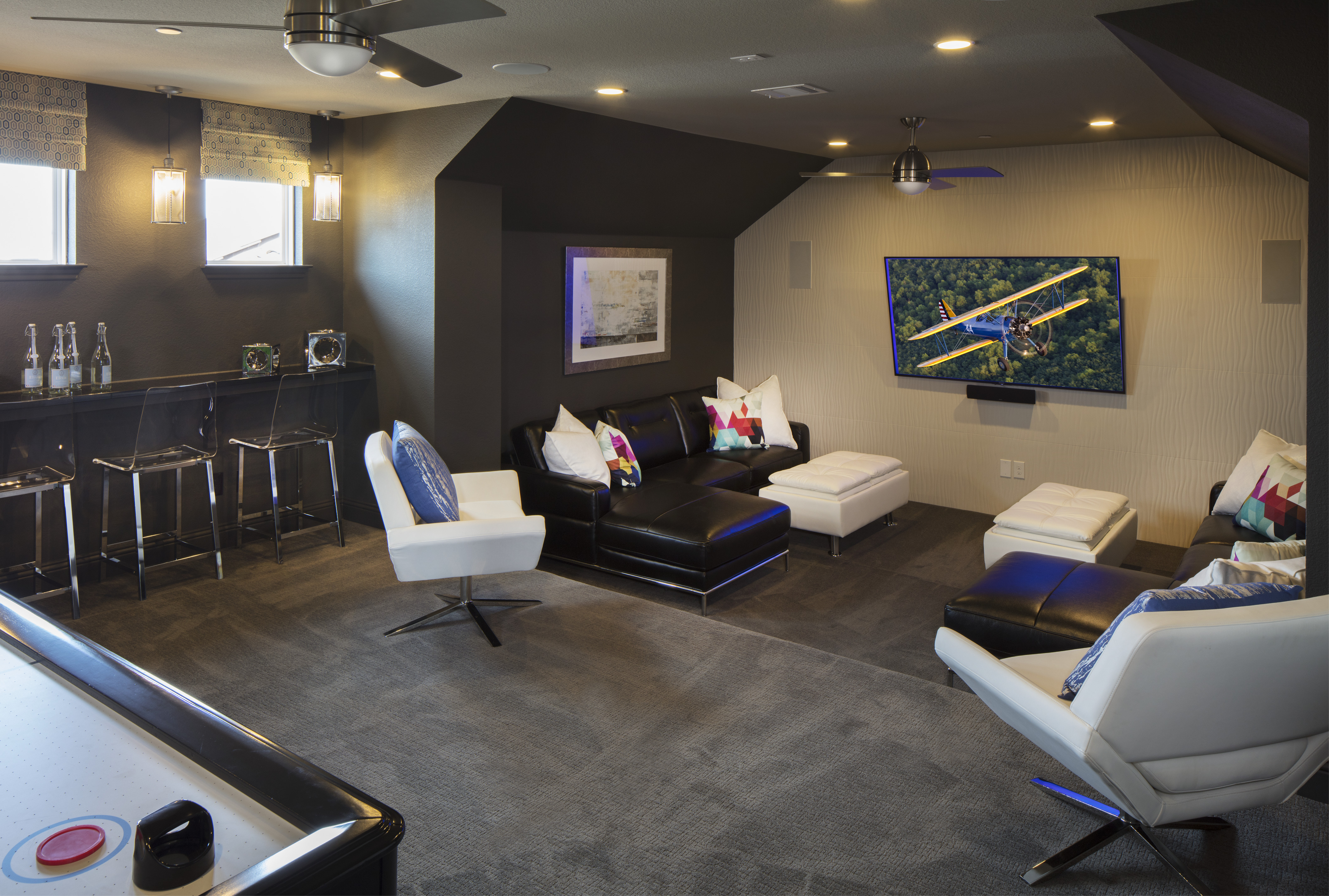 Basement game room with seats in front of a tv.