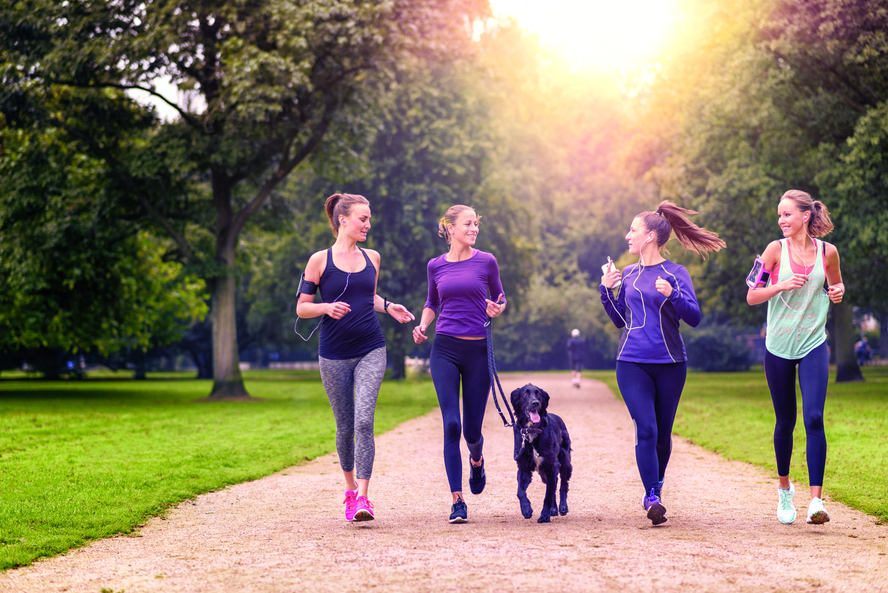 Four friends jogging with a dog in a park.