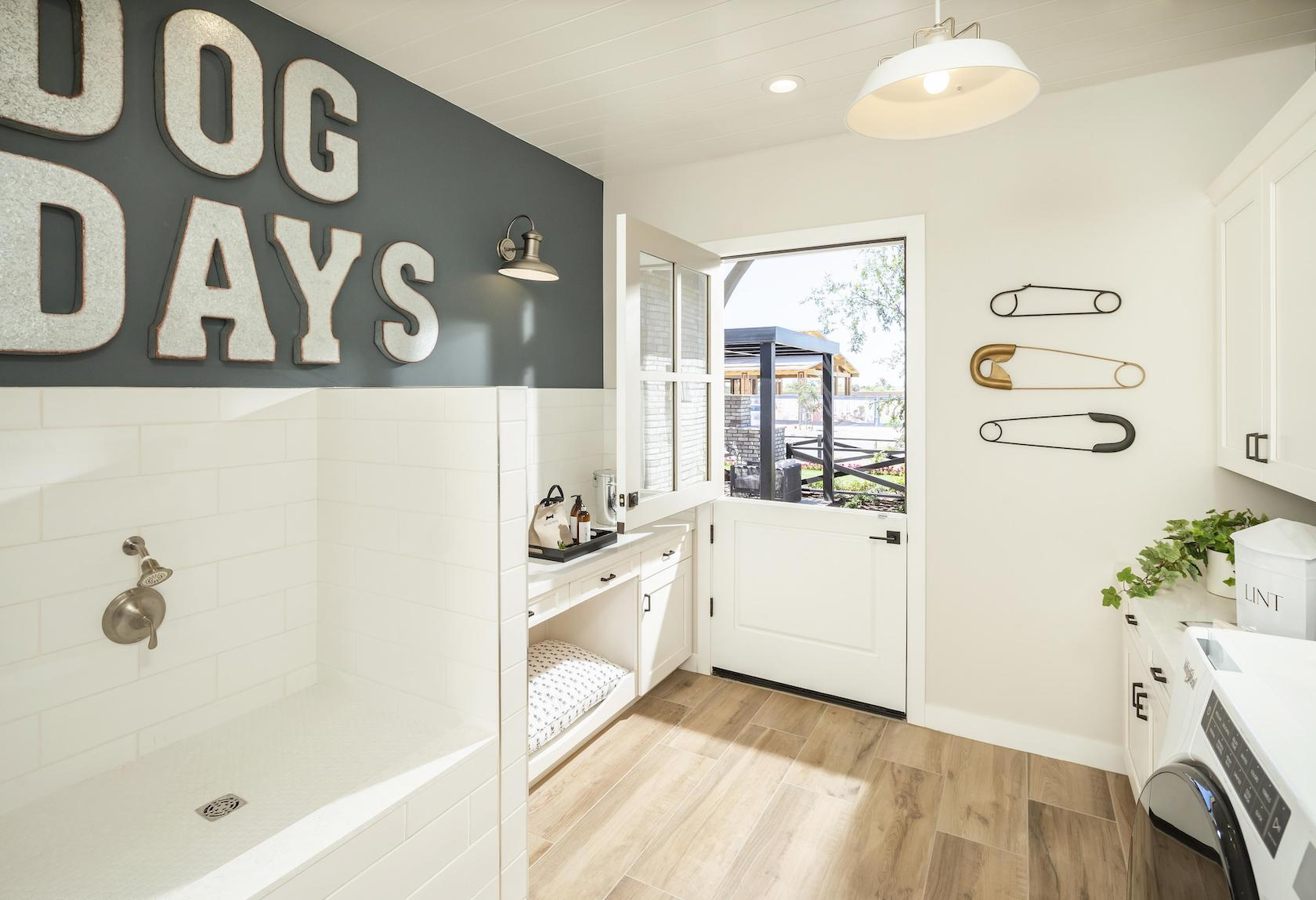 Laundry room with dog bed and shower.