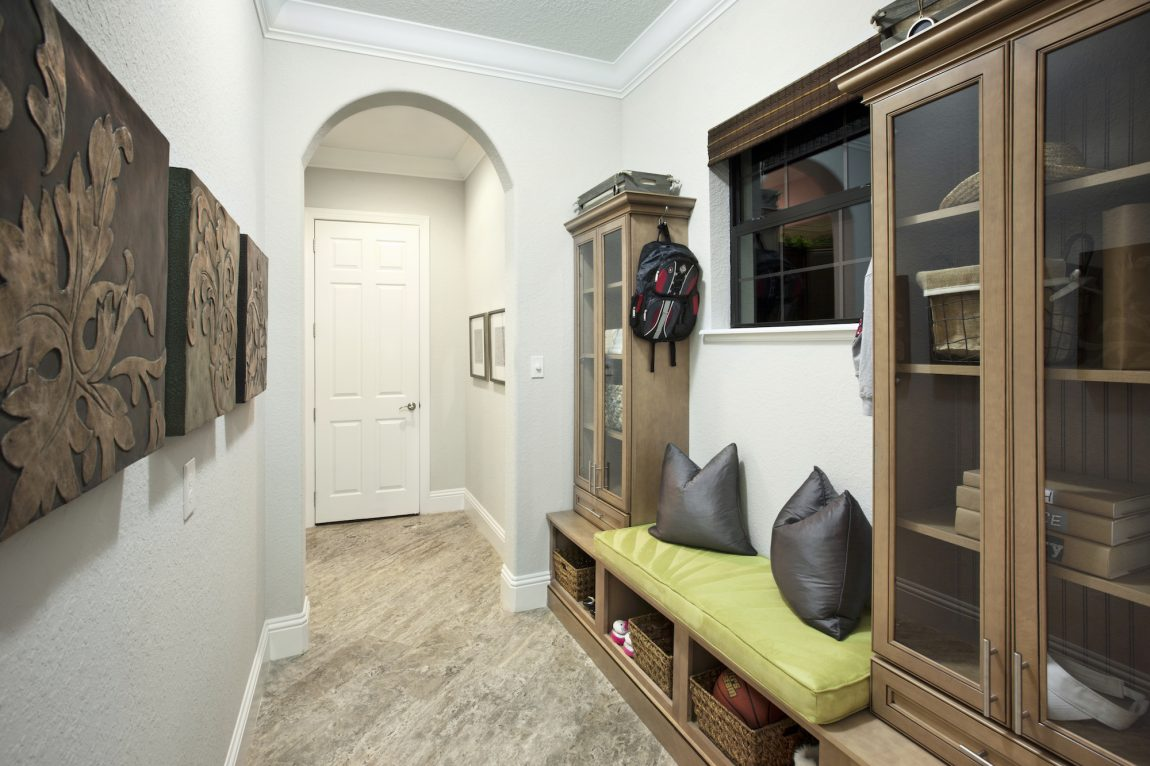 Mudroom with brown cabinets and a bench.