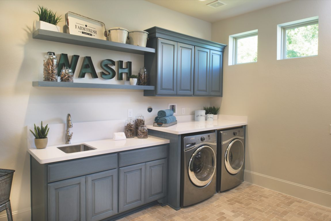 Mudroom with grey cabinets and laundry area.