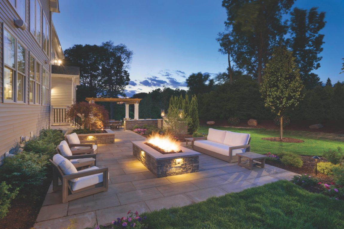 Outdoor fireplace with lush landscaping