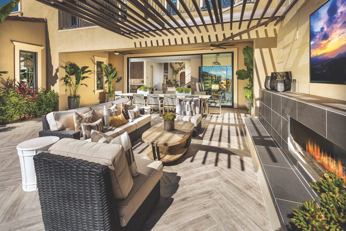 Backyard with a couch and chairs in front of tv.