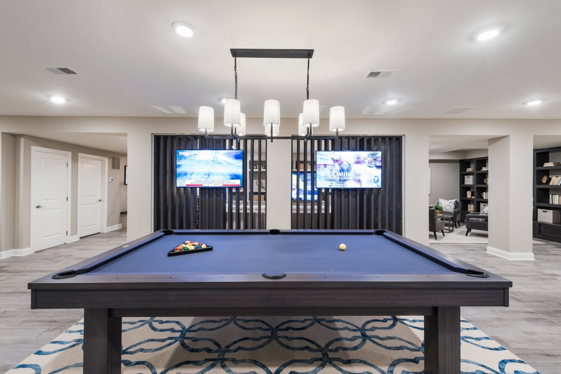 Basement with a pool table and television.