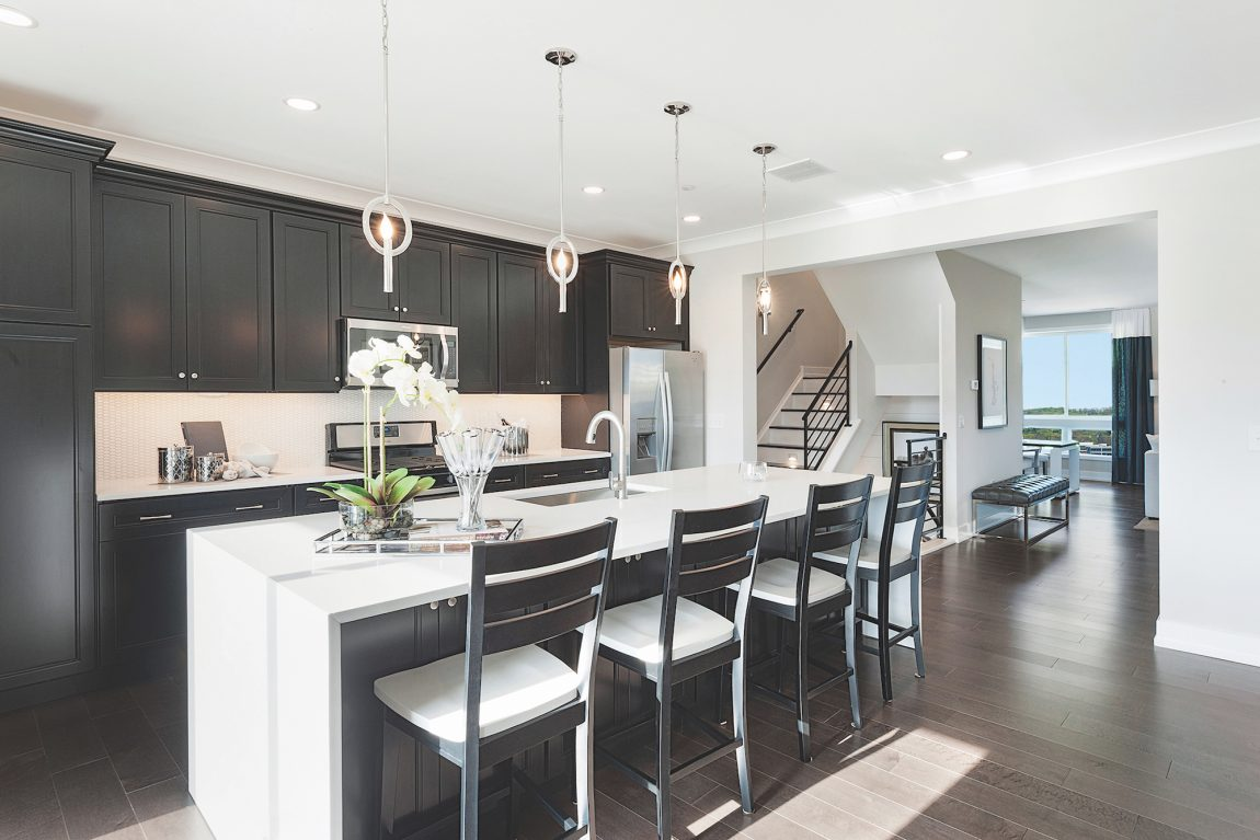 Kitchen with Dark Cabinets and White Waterfall Countertop