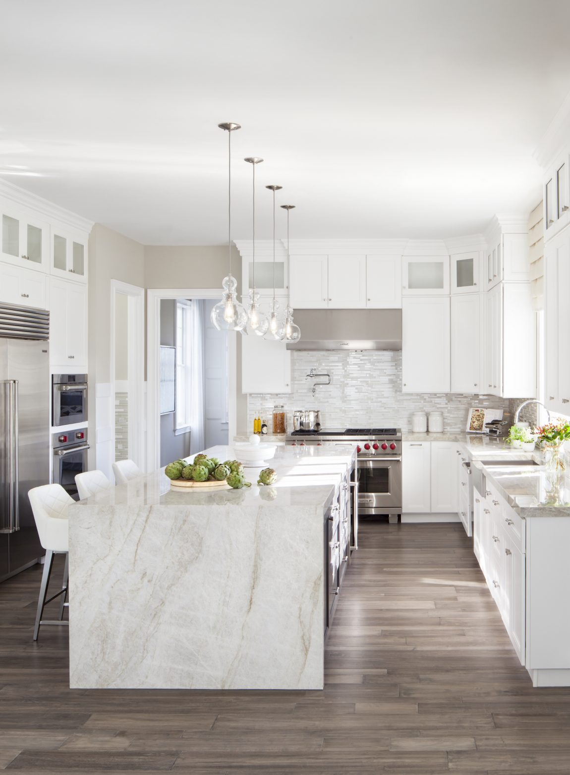 Kitchen with white cabinets and waterfall counter.