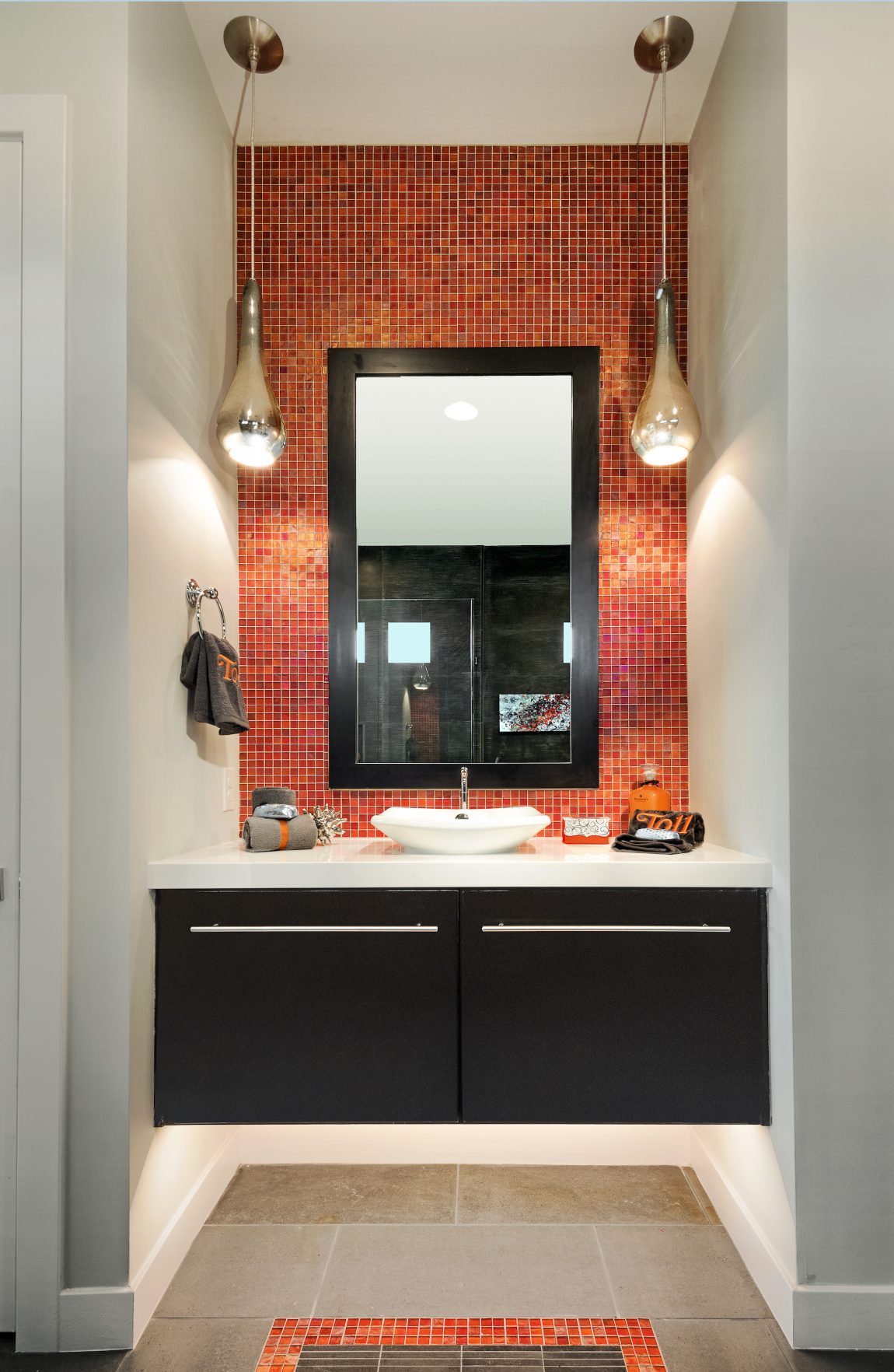 Small bathroom with an orange colored backsplash.