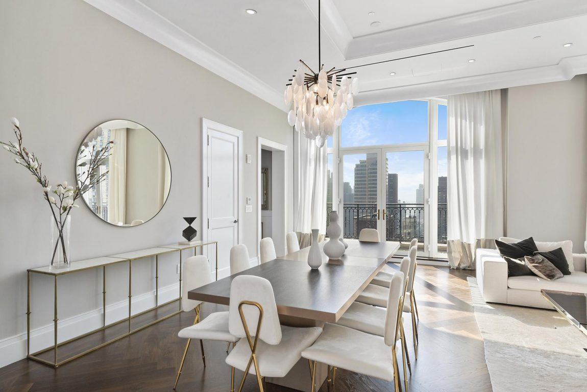 A dining room with a white color scheme and doors that open up to a terrace overlooking the city.