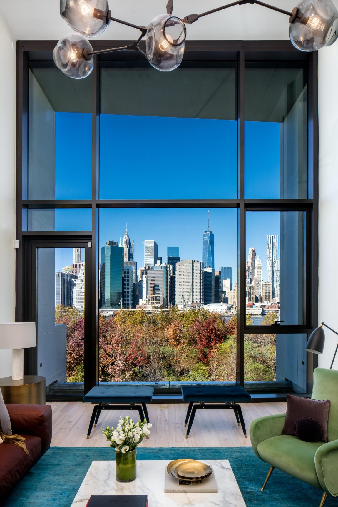 A grand living room window, and a view of New York City.,