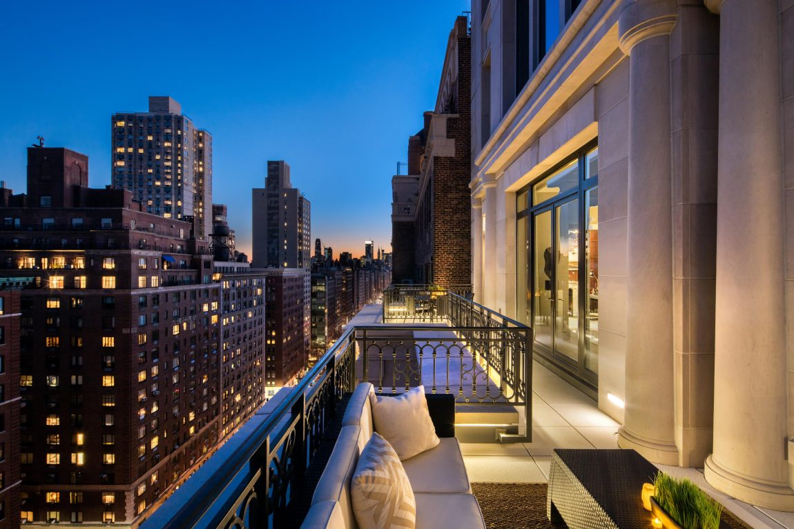 A highly elevated terrace overlooking adjacent cityscape at night.