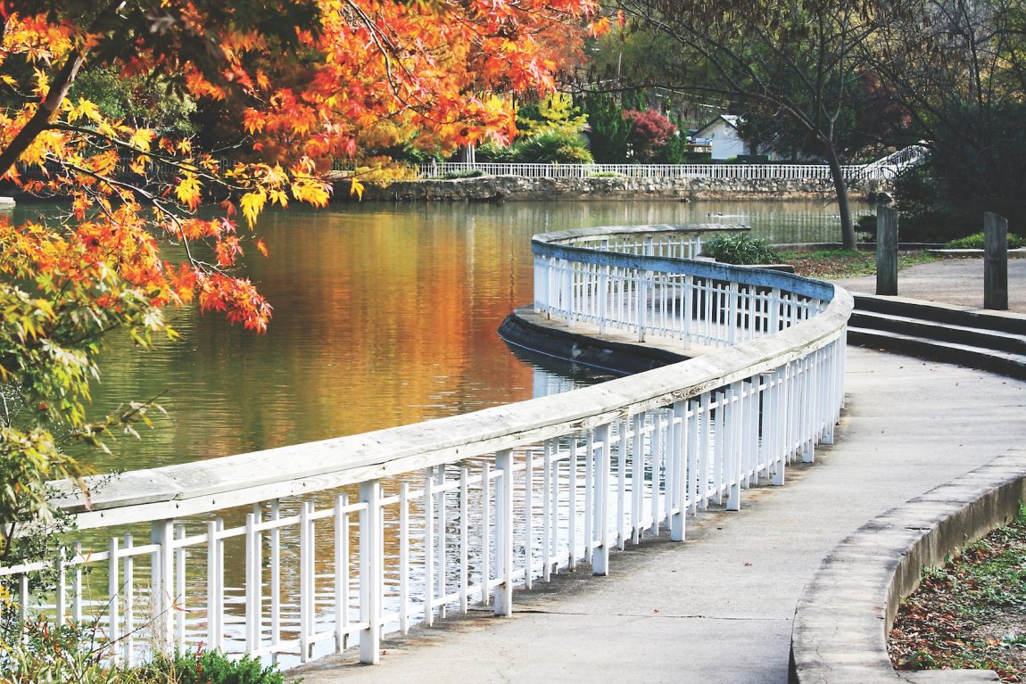 Scenic scene with white bridge with colorful fall trees