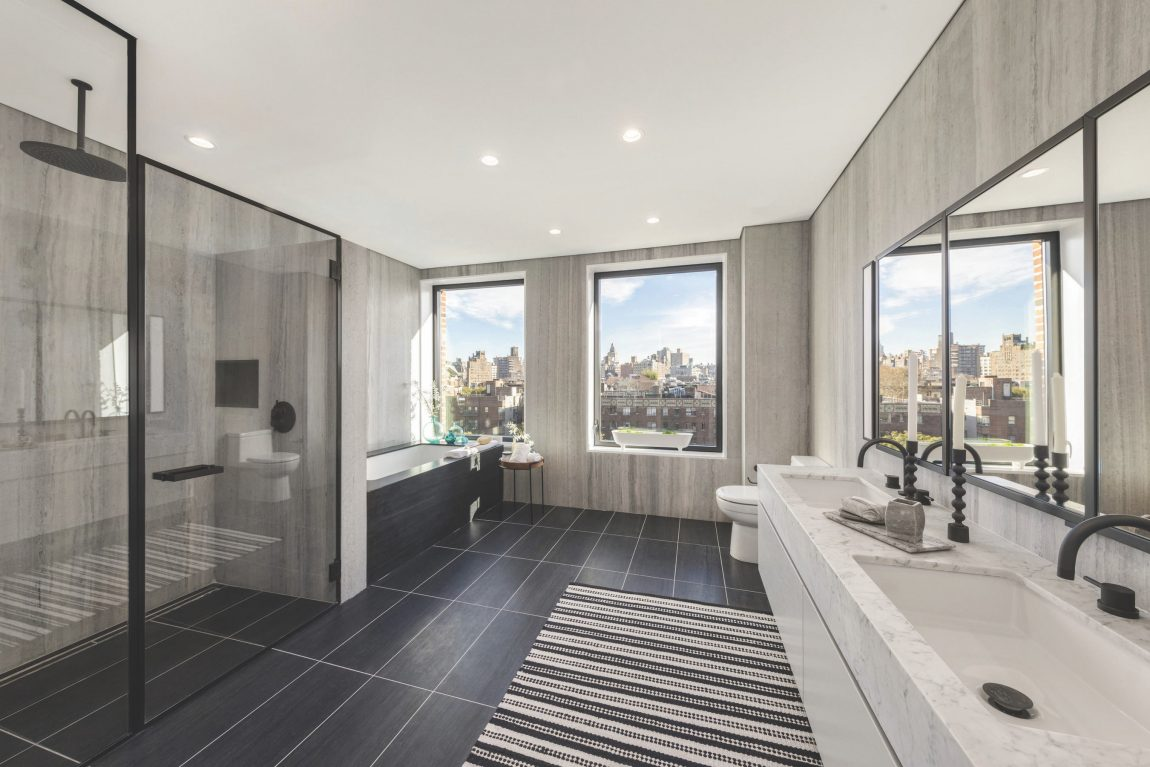A modern bathroom with a bath, standing shower, daul-vanity display, and window with a view of New York City