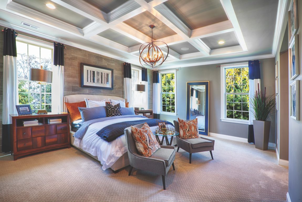Bedroom with ceiling beams, light fixture and colorful comforter