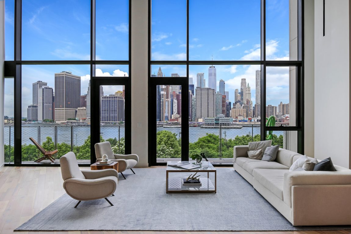 A modern living room with a view of the New York City skyline from across the river