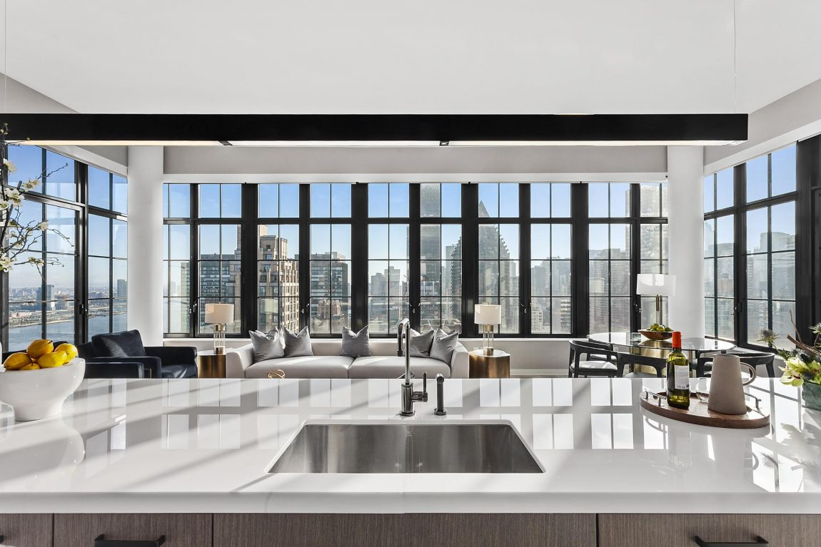 A kitchen island, seating area, and windows allowing for a panoramic view of the city.