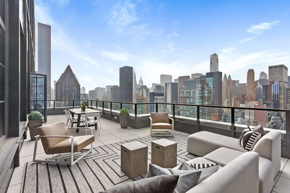 An outdoor terrace with a dining table and lounge area overlooking the cityscape