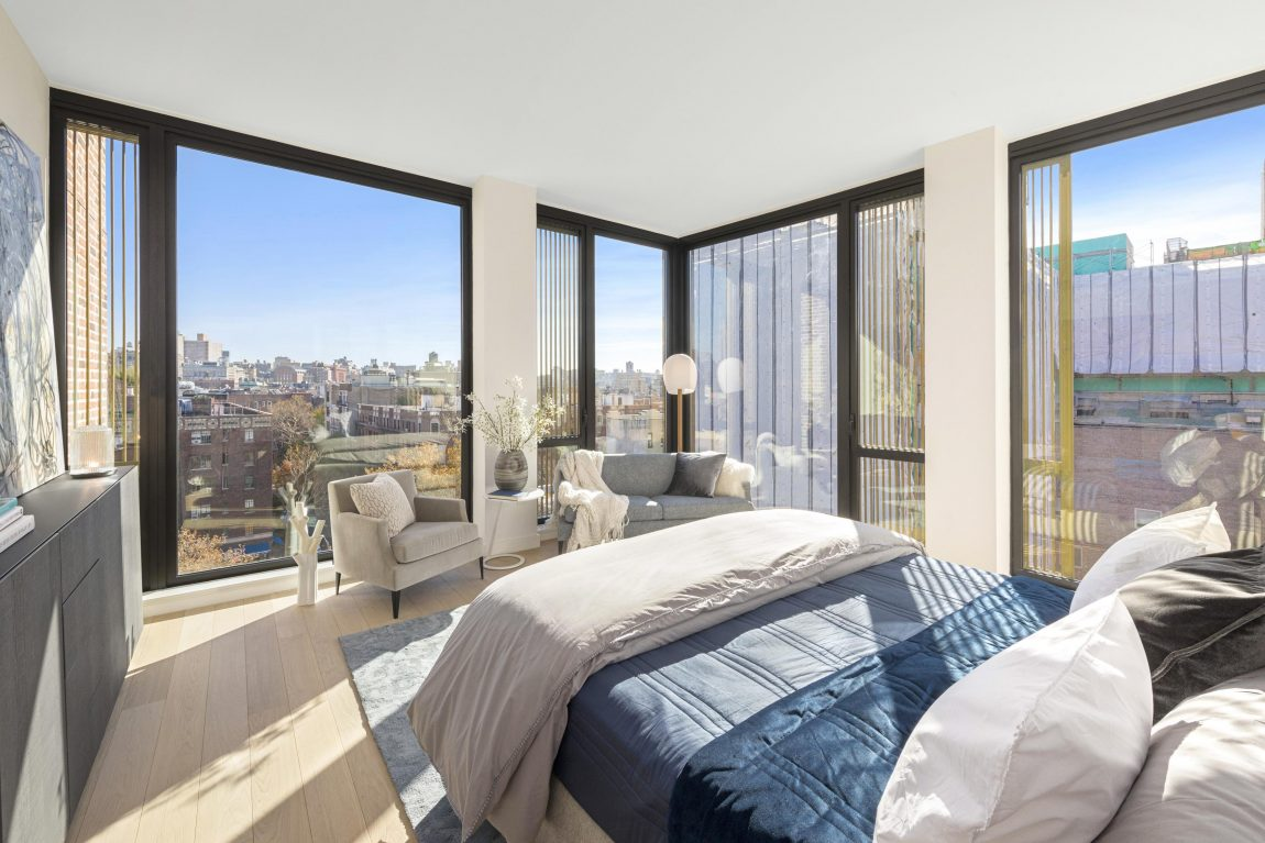 A bedroom with large windows and a view overlooking the city.