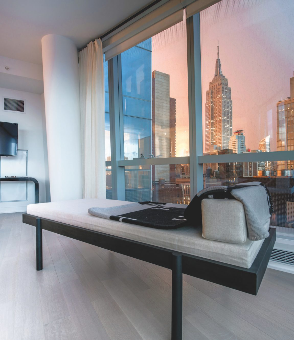 A modern couch next to a window with a view of the Empire Sate Building at sunset.